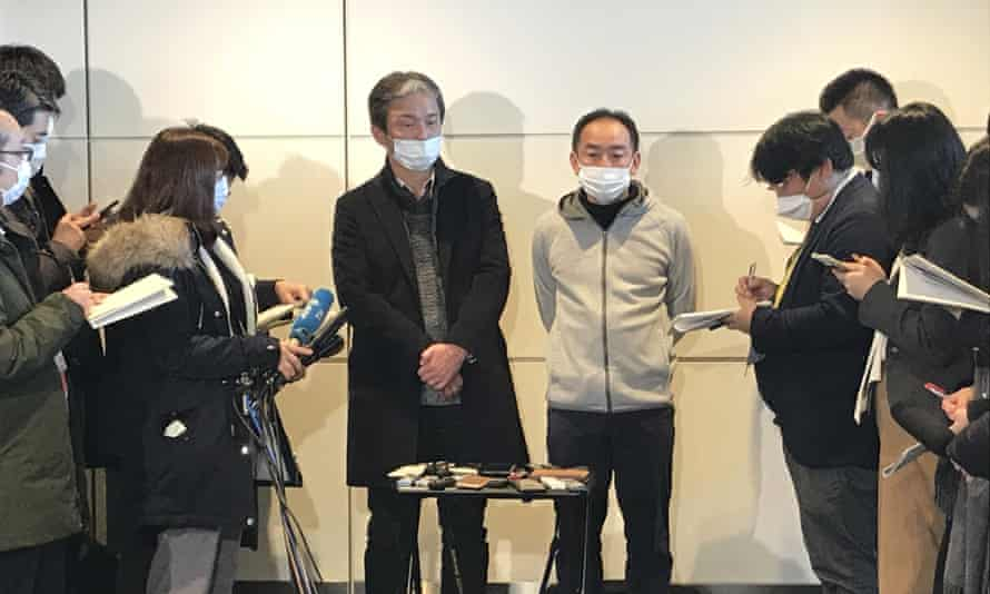 Wearing surgical masks, Takeo Aoyama, centre left, and Takayuki Kato, centre right, speak to journalists after returning home from Wuhan