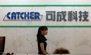 Employee walks past a logo of Catcher Technology at the company's headquarters in Tainan, southern Taiwan.