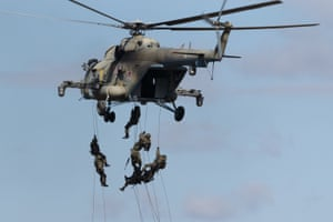 Military personnel fast-roping from a Mil Mi-8AMTSh-V multipurpose helicopter