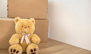 Teddy bear wooden floor alone cardboard boxes