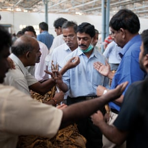 Periyapatna, India. P Jayarama (centre), auction superintendent of the Tobacco Board auction floor, accepting bids for the exhibited tobacco bales.