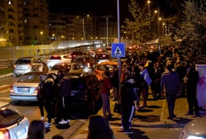 Dozens of residents standing at the side of a road at night