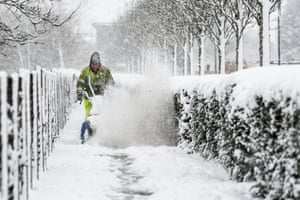 A council worker uses a machine to clear snow from pavements in Harthill, Scotland