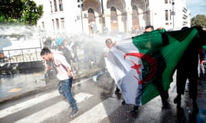 Algerian riot police spray anti-government protesters with water during a demonstration in the capital Algiers.