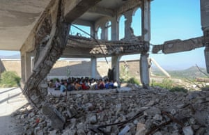 Pupils attend class on the first day of the new academic year in a makeshift classroom in their school compound which was heavily damaged two years ago in an airstrike.