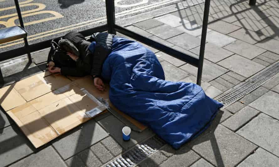 A homeless person sleeps on the street