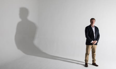 Stephen Fulcher standing with his arms folded in front of him and his long shadow to the left