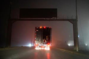 Central American migrants ride in the back of a lorry on their journey to the US.