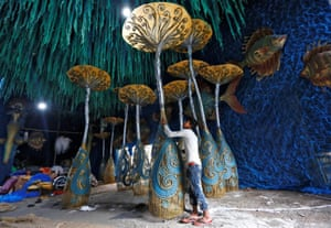 A worker decorates a pandal for the upcoming Hindu festival of Durga Puja