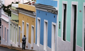 A pedestrian walks through a street in Old San Juan as Puerto Rico's economy continues to go downhill.