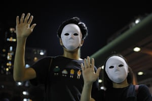 Masked protesters hold up their hands to represent their five demands during Saturday's rallies in Hong Kong.