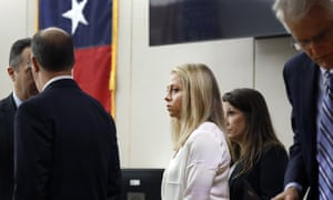 Amber Guyger, a former Dallas police officer, center, appears at the courthouse in Dallas on Saturday.