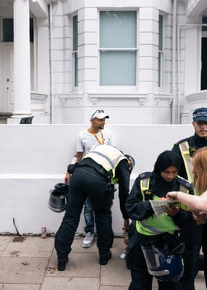 Police stop and search a man on Colville Terrace, while a woman asks for directions.