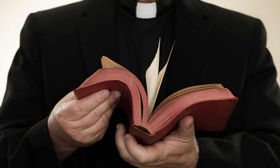 A priest holding a bible