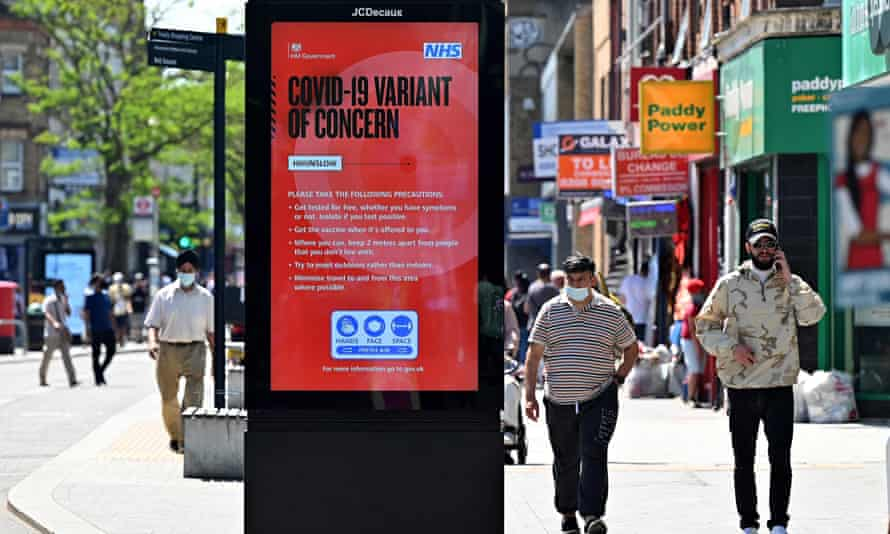 People walk past a sign warning about the spread of the new Delta variant of Covid-19 , in Hounslow, west London on 1 June.