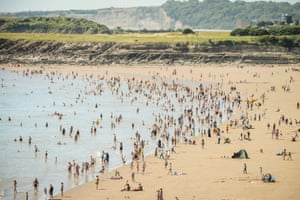 People enjoy the warm weather and sunshine on the beach at Barry Island, Wales