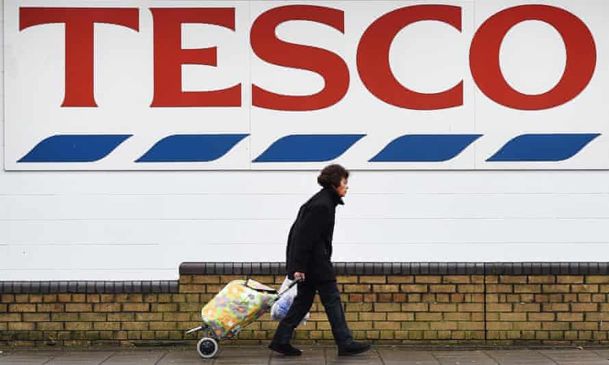 A pedestrian passes a Tesco supermarket store
