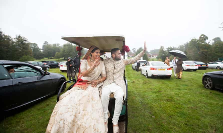 Roma Popat and Vinal Patel wave at guests from their golf buggy.