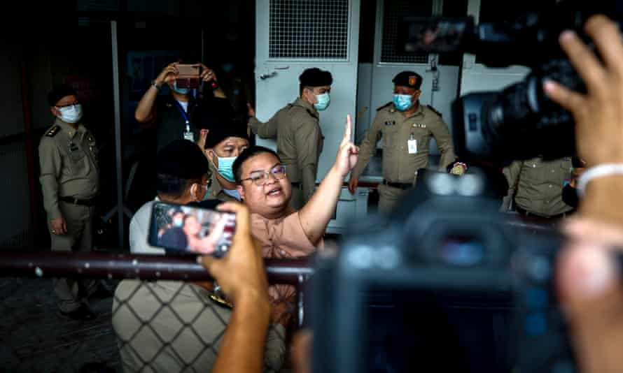 Parit 'Penguin' Chiwarak flashes the three-finger salute as he arrives to face charges in Bangkok