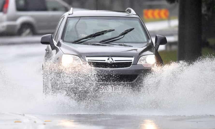 A car drives through a large puddle