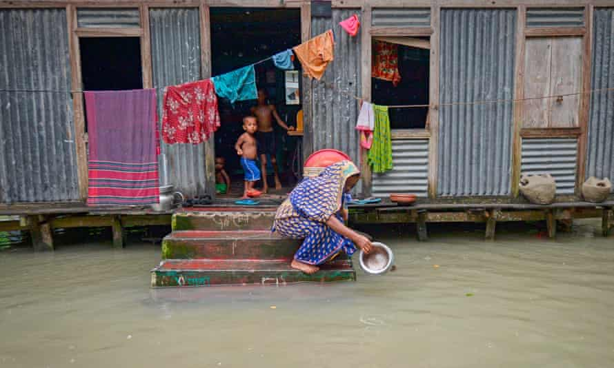 A woman washes a pot in flood water in Sreenagar, Bangladesh, after heavy monsoon rain last year.