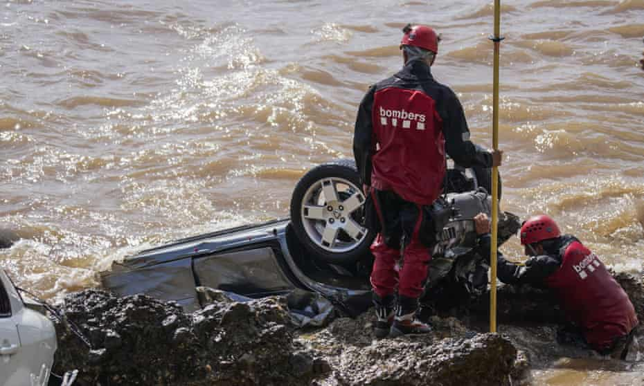 Firefighters check wrecked cars stuck on the shore of the seaside town of Alcanar in north-east Spain