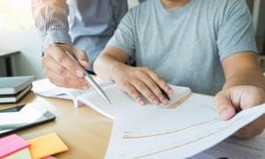 Teacher helps a teenage student revise