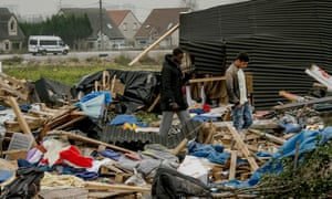 Refugees in the debris of the Calais camp on Tuesday.
