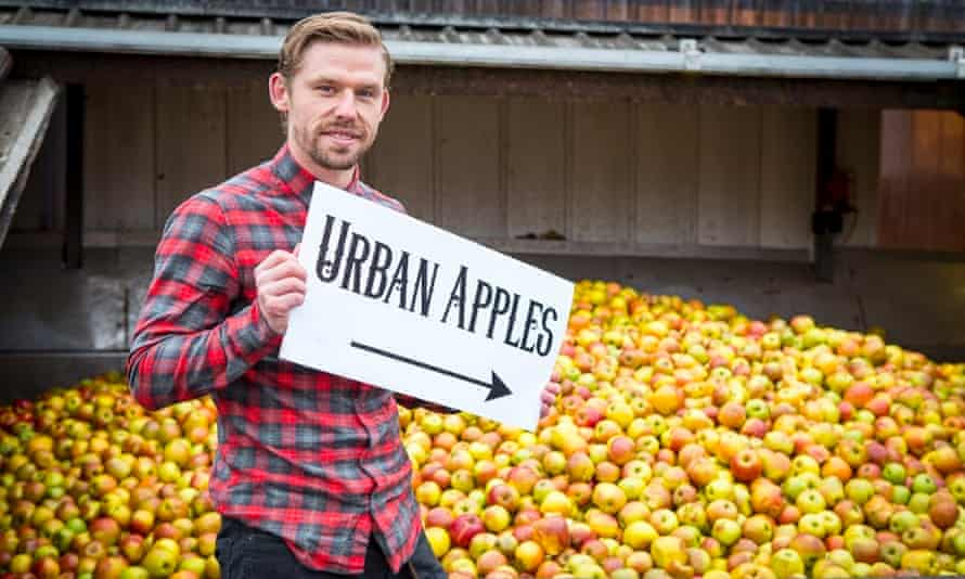 man in front of cider apples