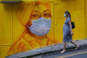 Hong Kong, China A pregnant woman wearing a face mask walks past a mural in Hong Kong