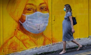 A pregnant woman wearing a mask walks past a street mural of a masked person in Hong Kong