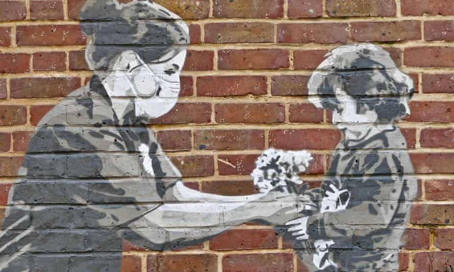 Artwork by Hendog on a brick wall at Winchester hospital shows a nurse helping a child