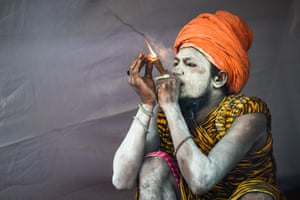 A sadhu smokes inside his tent.