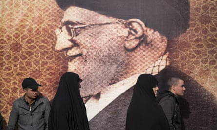 Iranians walk past a giant portrait of the country's supreme leader, Ayatollah Ali Khamenei.