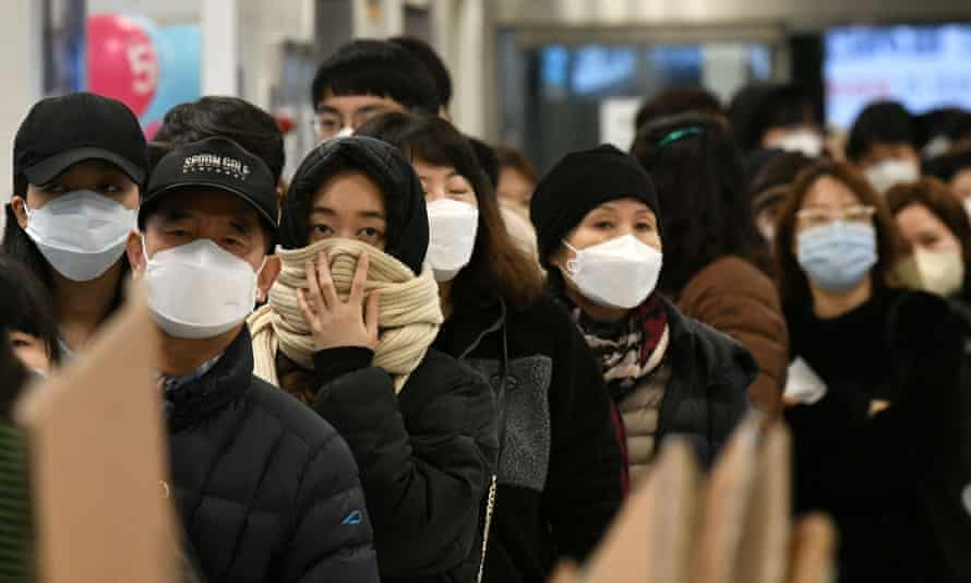 People wait in a line to buy face masks at a retail store in the southeastern city of Daegu