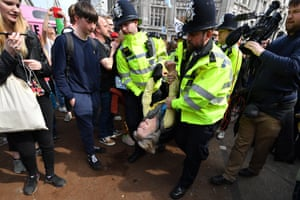 An Environmental campaigner is carried by police officers at Oxford Circus during the fourth day of a coordinated protest by the Extinction Rebellion group