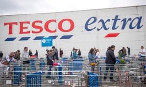 Shoppers queue outside a Tesco supermarket.
