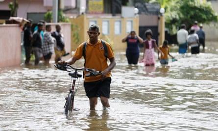 A man pushes his bike through a flooded road in Dodangoda village in Kalutara, Sri Lanka.