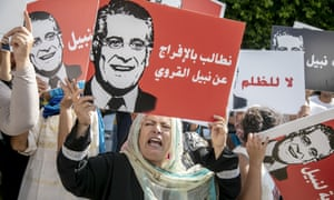 Supporters of Nabil Karoui hold up placards with his face