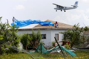 Devon Warner and his daughter Che Niesha work on the roof of a home in Codrington, Barbuda