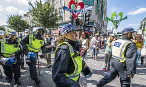 Riot police pass by the Grenfell quiet area after the minute's silence at the Notting Hill carnival last year.