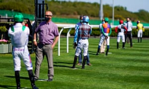 Jockeys observe social distancing guidelines at Newcastle Racecourse.