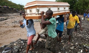 People carrying a coffin try to cross the river La Digue, after the passing of hurricane Matthew
