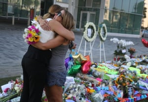 Two women comfort each other as they visit a memorial to honor the victims of the Pulse nightclub shooting.