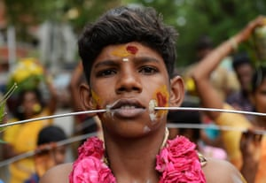 A devotee with a metal rod pierced through his mouth performs a ritual at the Aadi festival in Chennai, India