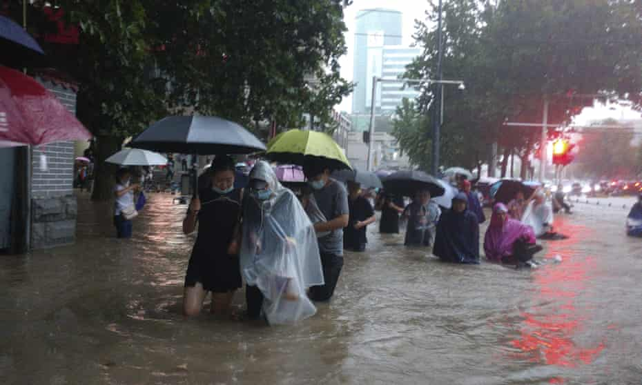People caught in flood water in Zhengzhou city in China's Henan province.
