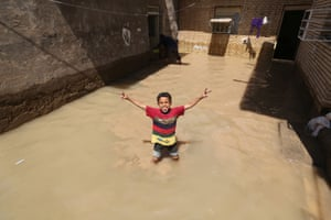 An Iranian child gestures for the camera at a flooded house in the city of Hamidiyeh, in Iran