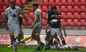 Wales' Louis Rees-Zammit celebrates with team mates scoring a try.