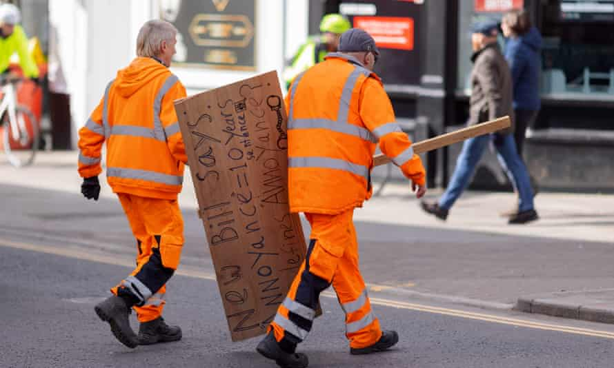 Workers remove a sign