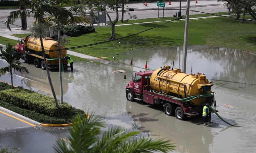 Workers use a vacuum truck to suck up sewer water that flooded the area at George English park after a sewer main broke in February 2020 in Fort Lauderdale, Florida.
